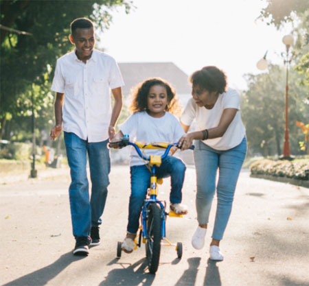 Parents teach a young African American girl how to ride a bike.