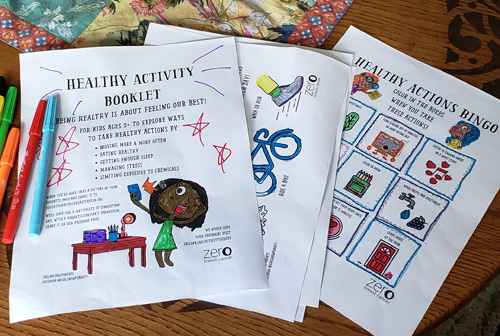 On top of a coffee table sits markers and ZBC's Healthy Activity Booklet pages that have been colored.