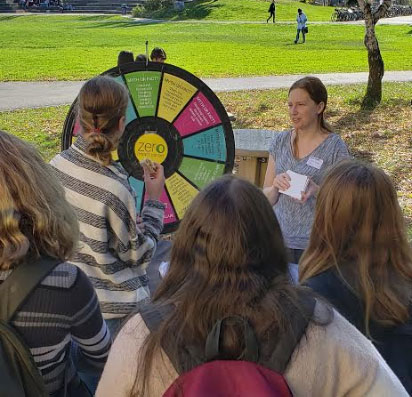 Lianna Hartmour stands next to a wheel that has questions about breast cancer on it. Four students participate in answering the question.